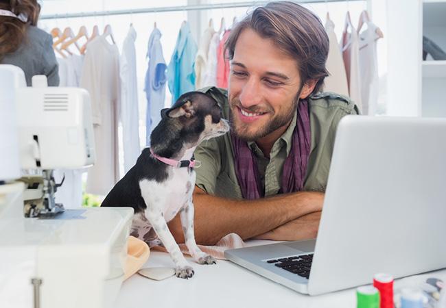 Молодой человек и его питомец в домашнем офисе