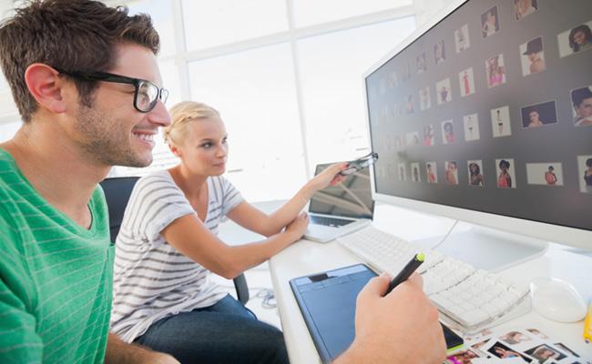 Молодые парень и девушка просматривают фотографии на компьютере