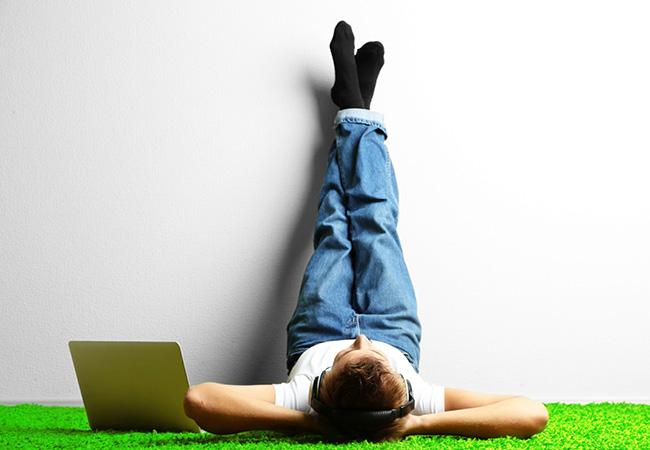 Молодой человек отдыхает рядом со своим ноутбуком