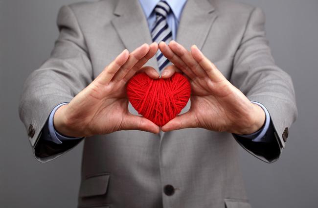Безнесмен с красным сердечком в руках