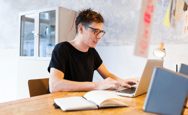 молодой человек работающий в очках за ноутбуком