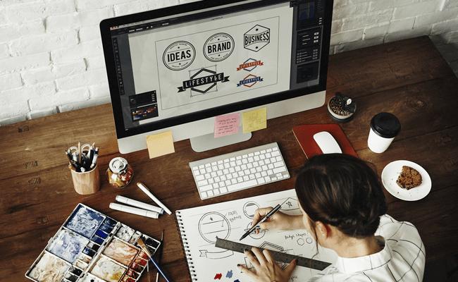 дизайнер за рабочим столом подберает подходящие шрифты
